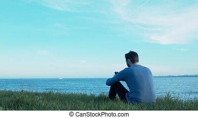 trawa, słuchający, headphones., posiedzenie, pozwy, przelotny, niebo, młody, przez, samolot, muzyka, morze, sms., chwilowy, przystojny, łódka, człowiek