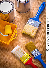 tray roller paint brushes cans on wooden board