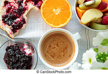 Tray with bread with jam, fruits, sliced orange and cup of coffee