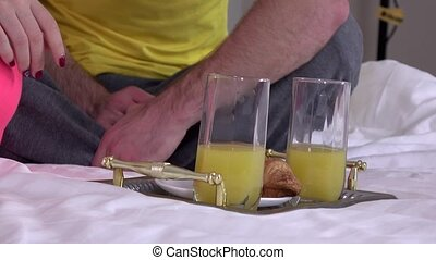 Tray with breakfast on a bed, closeup