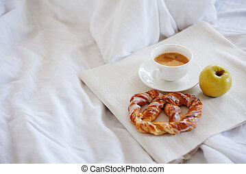 Tray with breakfast on a bed. Sweet pretzel, Cup of coffee and Apple