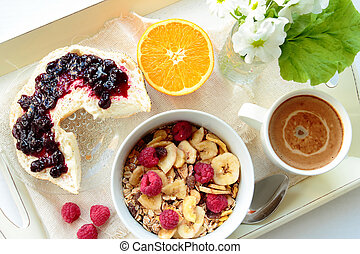 Tray with cereals with berries, roll with jam and sweet coffee