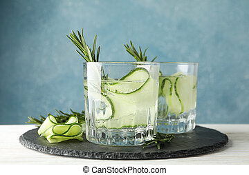 Tray with glasses of cucumber water on wooden table, close up