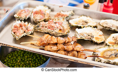 Tray with shish kebab from scallops and baked oysters -...