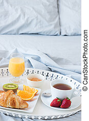Tray with tasty breakfast on a bed