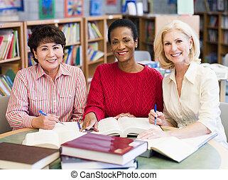 tre donne, seduta, in, biblioteca, con, libri, e, notepads, (selective, focus)