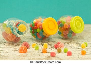 tre, exponeringsglaskrus, fyllda, av, jellybeans, med, blåttbakgrund