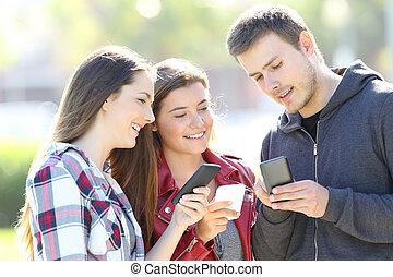 tre kamrater, talande, holdingen, deras, smart, telefoner