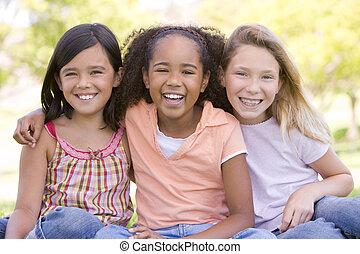 tre, ung flicka, vänner, sittande, utomhus, le