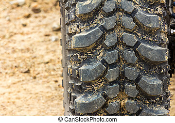 Tread tire coated in mud on an offroad