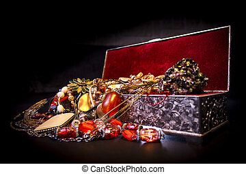 Silver treasure box in the dark, full of necklaces and jewelery