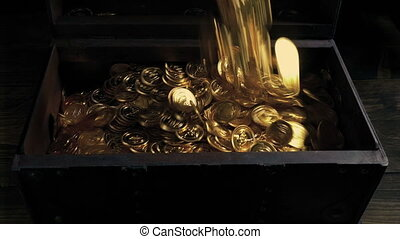 Gold treasure coins are poured into an old wooden chest