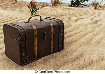 Treasure chest in sand dunes on the beach