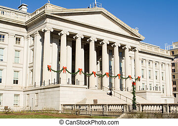 Treasury building in Washington DC decorated for Christmas.  String of pine garlands with red bows attached to the columns of the facade.