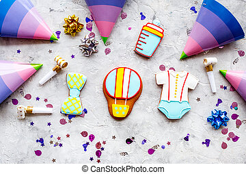 treat for baby birthday party with gingerbread cookies on stone background top view pattern