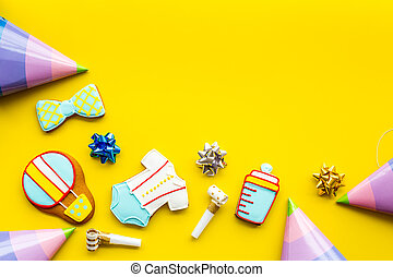 treat for baby birthday party with gingerbread cookies on yellow bright background top view mock-up
