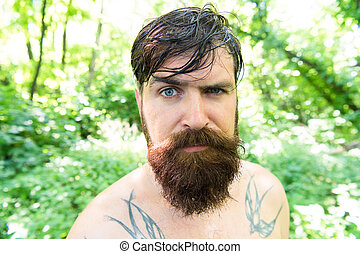 Treat your hair today. Bearded man with wet oily hair on natural environment. Hairy hipster wearing shaped beard and styled mustache hair. Antigrease shampoo and oil hair treatment.