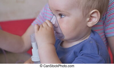 Treatment of lung disease with an inhaler. A little boy in the mask of an inhaler. Treatment at home.