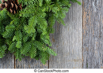 Tree branch with pinecone on rustic wooden background used for c