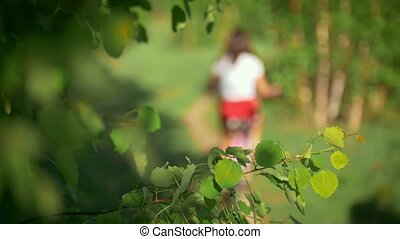 Tree branches in the wind, background of young girls riding bicycles, blurred, green forest, summer day