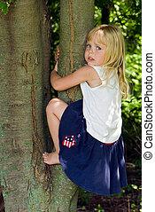 Little girl climbing a tree.