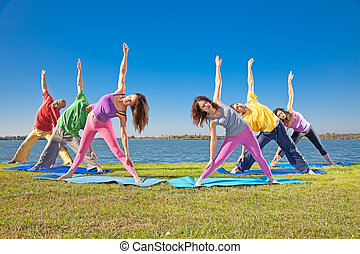 Tree couple , man and woman practice Yoga asana on lakeside. Yoga concept.