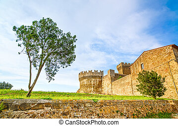 Tree in Populonia medieval village landmark, city walls and tower on background. Tuscany, Italy.