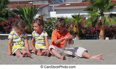 Tree kids boy and two girls sitting on sand - Three kids boy...