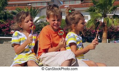 Tree kids boy and two girls eating lolly candy sitting on sand