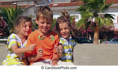 Tree kids boy and two girls sitting on sand and showing lolly candy to each other