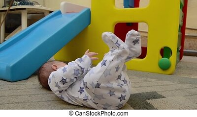 tree months old baby boy streching his legs on the carpet in backyard while plastic play house is in the background