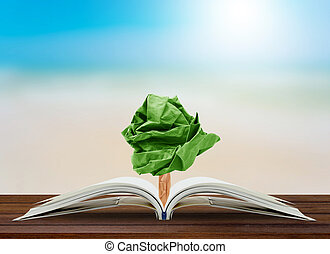 Tree paper growing from book on table, concept conservation of the environment, environmental protection