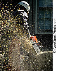 Tree service worker. A shower of wood chips sprays from the chainsaw as it bites into the log.