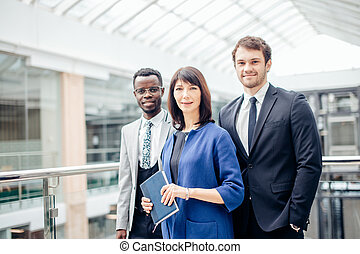 tree successful businesspeople, business team posing in modern office