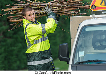 tree surgeon putting branches in his car