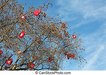 Tree with red hearts on a background of blue sky