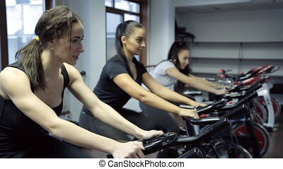 Tree women do exercises on exercise bike in fitness center.