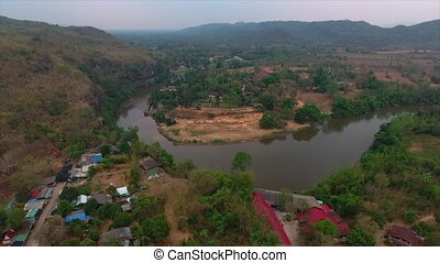 Trees and houses on a riverbank - A birds eye view of green...