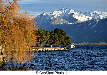 Snow-capped mountains and an alpine lake with treesin autumn