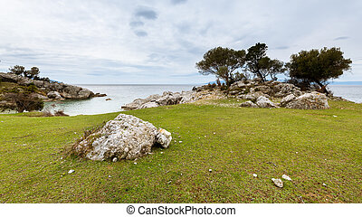 Trees and rocks near small bay of Sveti Blaz on a cloudy day in spring