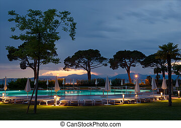 trees at swimming pool at sunset with loungers
