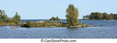 Trees growing on rock formations and small islands near the shore of Lake Vanern.