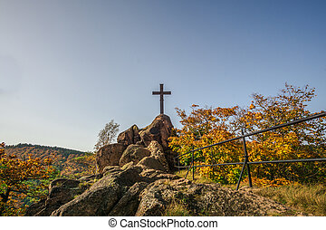 Trees in colorful autumn colors and a cross on a rock