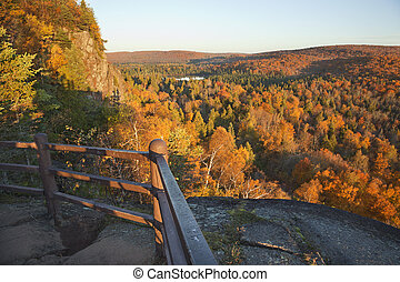 Trees in fall color, hills and lake viewed from a scenic overlook in northern Minnesota