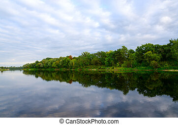Trees on bank of pond and clouds are reflecting in water