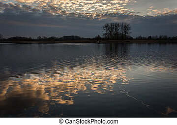 Trees on the shore of the lake and reflection of clouds in the water