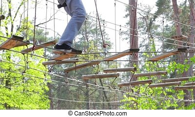 Treetop adventure park at daytime. Ropes and wooden planks. ...