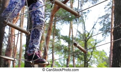 Treetop adventure park. Legs of person in motion. Not afraid...