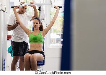 treinador pessoal, ajudando, mulher, treinamento, em, wellness, clube