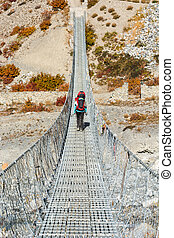Trekker crossing metal suspension bridge.